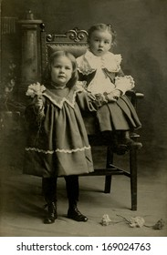 USA - NEW YORK - CIRCA 1895 - A vintage antique photo of two little girl's dressed in Victorian style dress. One is standing and the other one is sitting in. A photo from the Victorian era. CIRCA 1895