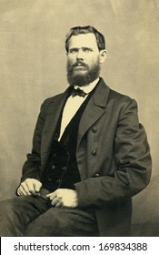 USA - NEW YORK - CIRCA 1898 - A vintage photo of a young man. The man is sitting. He has a beard and mustache and is dressed in suit and vest with bow tie. A photo from the Victorian era. CIRCA 1898