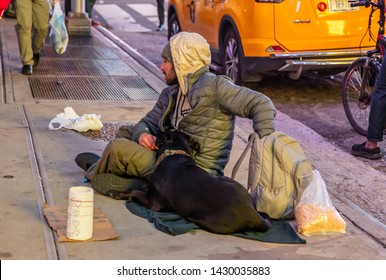 USA, New York. May 3, 2019. Homeless man and a dog sitting on the sidewalk, asking for help, Manhattan downtown