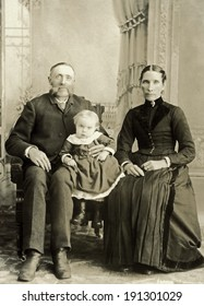 USA - NORTH DAKOTA - CIRCA 1895 A vintage photo of a Victorian family. The parents or grandparents are older with a small child. The man has a mustache. Photo is from the Victorian era. CIRCA 1895