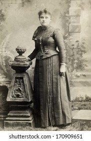 USA - OHIO - CIRCA 1885 - A vintage photo of a young woman. The woman is standing next to a studio prop and dressed in a beautiful Victorian style dress. A photo from the Victorian era. CIRCA 1885