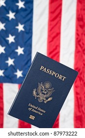 A USA passport with an American flag in the background