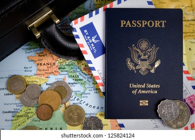 USA passport, foreign coins and briefcase sit on a world map for an international business travel concept.