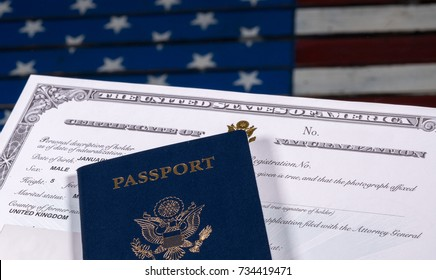 USA passport and Naturalization Certificate of citizenship over background of a wooden US Stars and Stripes flag