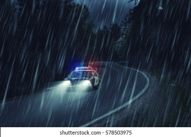 USA police car at work at night in the forest, heavy rain, motion blur