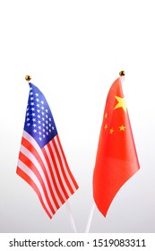 USA and PRC. Two table flags on a white background. The government of China and America is in talks. The concept of a meeting of American and Chinese colleagues or officials. Copy space.