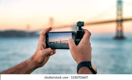 USA, San Francisco - August 2019: A photographer is using DJI Osmo Pocket to take footage of a Bay Bridge