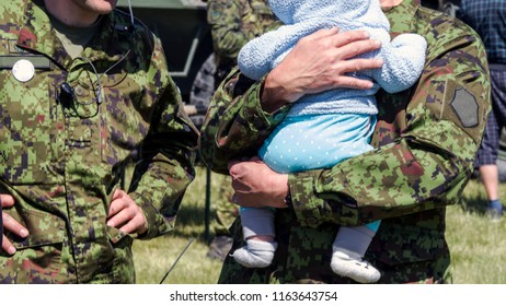 USA Soldier reunited with his little baby on a sunny day  on a sunny day with military equipment on the background. concept of salvation and liberation or rescue, danger, accident and military
