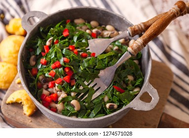 USA Southern New Year's Day Dish of Collard Greens, Black Eyed Peas Topped with Red Pepper and Cornbread in a Rustic Pot
