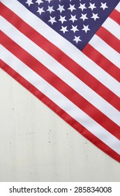 USA stars and stripes flag on white wood background with copy space for Fourth of July and National holidays.