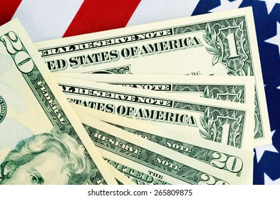 USA Tax Day, April 15, or money, savings and finance concept with USA dollar notes on American flag.