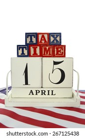 USA Tax Day, April 15, concept with vintage style calendar and Tax Time blocks on flag on blue wood background.