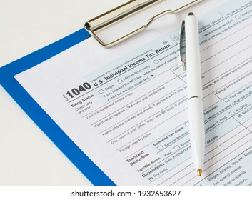 USA tax form 1040 with eyeglasses and Pen on a clip board. Can be use as a concept photo