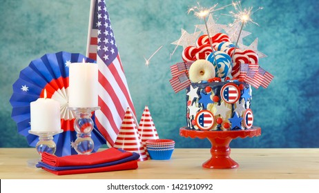 USA theme on-trend candyland fantasy drip cake with lollipops and candy decorations in colorful party table setting.