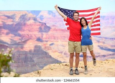 USA travel tourist couple holding american flag in Grand Canyon. Happy young multiethnic couple cheering at Grand Canyon south rim during summer holidays.