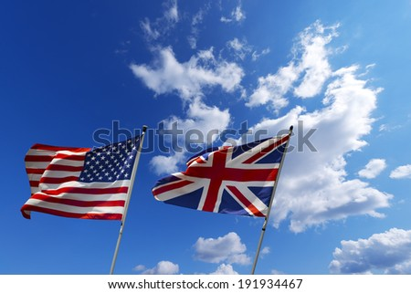 USA and UK flags in the blue sky / English and American flag waving in the wind on blue sky with clouds - U.S.A. and UK