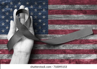 USA United Stated of America 9/11 remembering and National POW/MIA recognition day concept with Black awareness ribbon on people's hand support on American flag