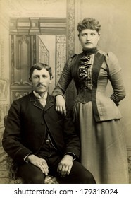 USA - VERMONT - CIRCA 1890 A vintage Cabinet Card photo of a young couple. They are dressed in Victorian style clothing. She is standing and he is sitting. A photo from the Victorian era. CIRCA 1890