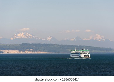 USA, Washington State, Whidbey Island. State ferry transports cars and passengers between Whidbey and Port Townsend with majestic vistas of North Cascades beyond.