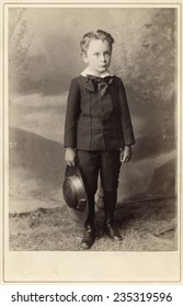 USA WISCONSIN CIRCA 1895 Vintage Cabinet Card of a small boy child standing holding a hat. He is dressed in a suit with a bow tie and boots.  Photo from the Victorian era. Circa 1895
