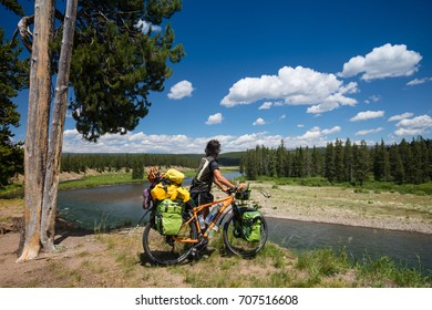 USA.2017 Year,July .15 .A tourist on a bicycle on a river in Yellowstone Park