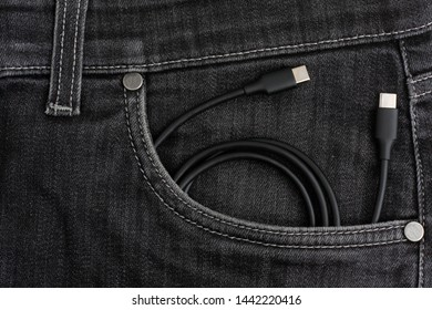 USB cable lies in black jeans pocket.