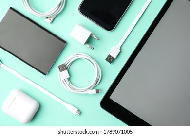 USB charge cables, power adapter and gadgets on light blue background, flat lay. Modern technology