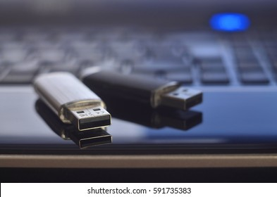 USB flash cards lying on black laptop case in front of his keyboard. Virtual memory storage with USB output