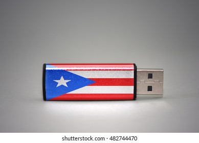 usb flash drive with the national flag of puerto rico on gray background. concept