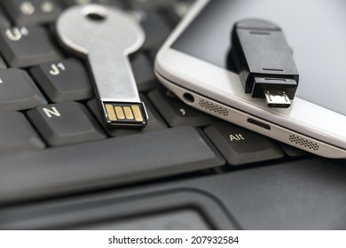 USB key and smartphone with micro USB flash drive on laptop keyboard