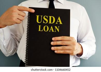 USDA Loan concept. Man holding book.