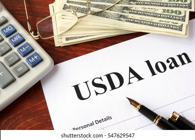 USDA loan form and documents on a table.