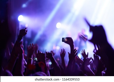 Use advanced mobile recording, fun concerts and beautiful lighting, Candid image of crowd at rock concert, Close up of recording video with smartphone, Enjoy the use of mobile photography.