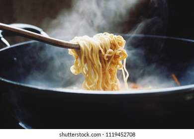 Use chopsticks to handle noodles. In a pot with smoke on an Asian stove on a junk food concept