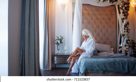 To use the cream for the body. Young woman in a Bathrobe, interior of the hotel