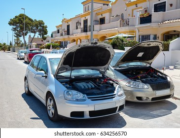 Use an external car battery to start the engine of the vehicle of the other car. Charging automobile discharged battery by booster jumper cables. Trying to jump start a cars.