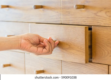 Use hand pull open drawer wooden in cabinet.