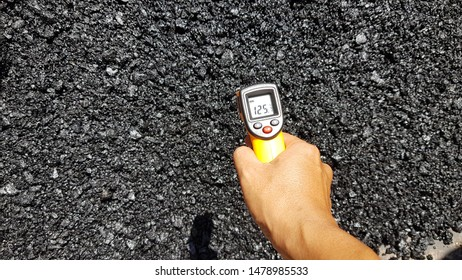 Use a infrared thermometer to measure the temperature of hot mix asphalt.