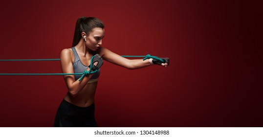 Use it or lose it. Sportswoman performs exercises with resistance band over red background