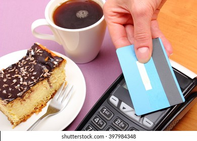 Use payment terminal with contactless credit card with NFC technology for paying in cafe or restaurant, cheesecake and coffee, finance concept