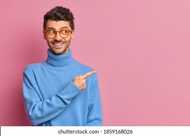 Use this copy space wisely. Glad handsome man in casual outfit points away on right advetises something smiles happily wears blue turtleneck isolated over pink background shows good offer to you
