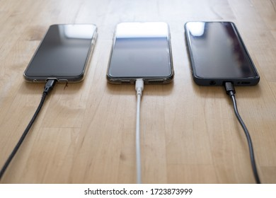 Use USB and lightning cables to charge three phones at the same time in a house.
