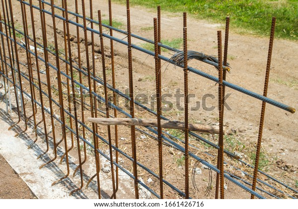 Use of Wire to Bind a Steel Bar to Build a Wall Foundation. Building the foundation for strength. The building is delayed until iron rust occurs.