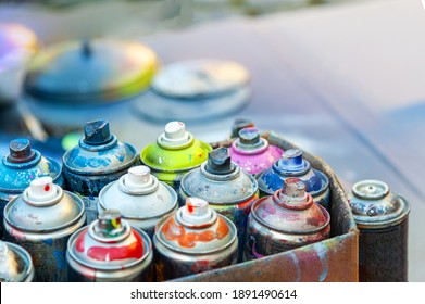 Used aerosol spray paint in cans in carton .
