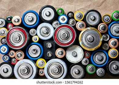 Used Alkaline batteries of various types (C AA AAA D 9V) on recycled paper ready for recycling - toxic waste and environmental issues concept