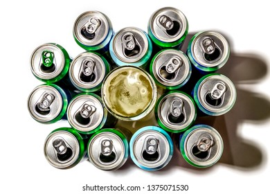 Used aluminum cans of beer and a glass of beer stand in rows on a light background