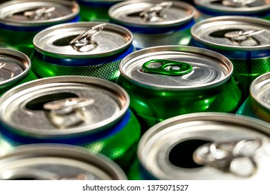 Used aluminum cans of beer stand in rows on a light background