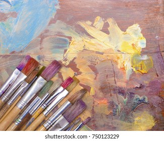 Used artists paint brushes different colors on palette background