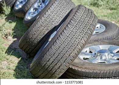 Used automotive tires with rims stacked on grass with shallow depth of field