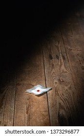 Used bandage with blood fallen on wooden floor in strip of light. Top view.